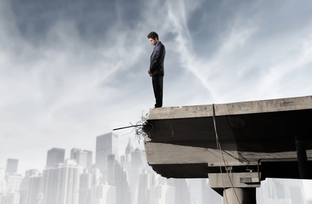 sad businessman: Sad businessman standing on the edge of a broken bridge with cityscape on the background Stock Photo