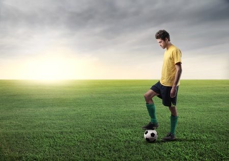 boys soccer: Football player on a green meadow Stock Photo