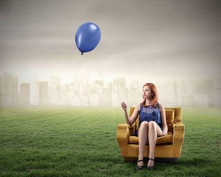 huir: Mujer sentada en un sill�n en un prado verde y la celebraci�n de un globo con el paisaje urbano en el fondo