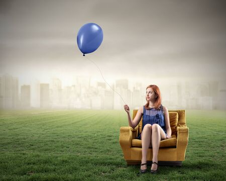 city trip: Woman sitting on an armchair on a green meadow and holding a balloon with cityscape on the background