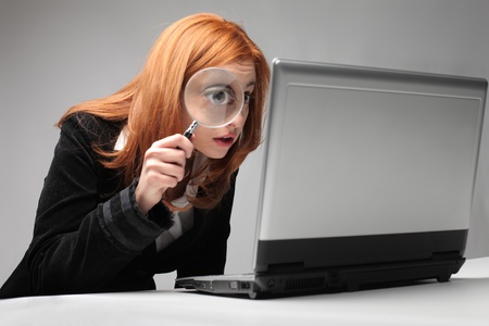 magnifying glass: Young businesswoman observing a laptop with a magnifying glass Stock Photo