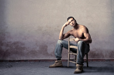 muscle toning: Handsome young man sitting on a chair
