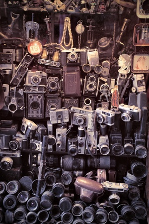 reflex camera: Old cameras on a stand in a marketplace Stock Photo