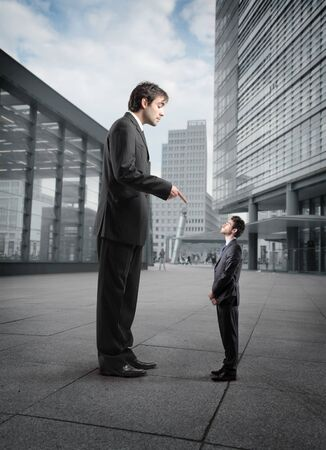 scold: Giant businessman scolding a smaller one