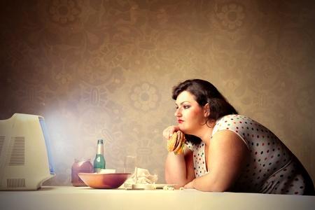 mujer gorda: Grasa mujer viendo la televisi�n mientras una hamburguesa Foto de archivo