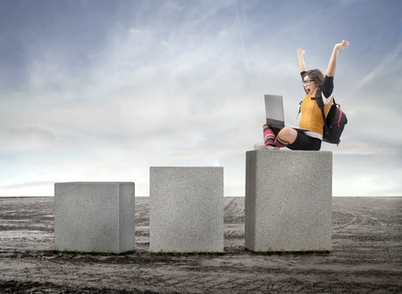 triumphing: Triumphing student with laptop sitting on a cube Stock Photo