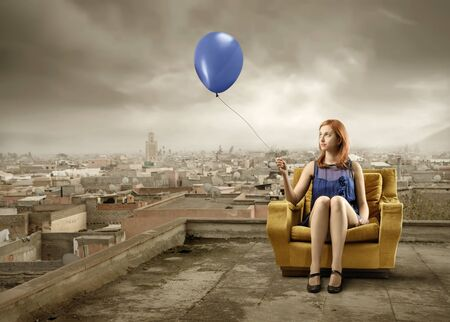 degradation: Elegant woman sitting on an armchair and holding a balloon with cityscape on the background