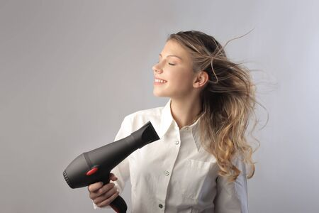 hairdryer: Beautiful woman using a hairdryer Stock Photo