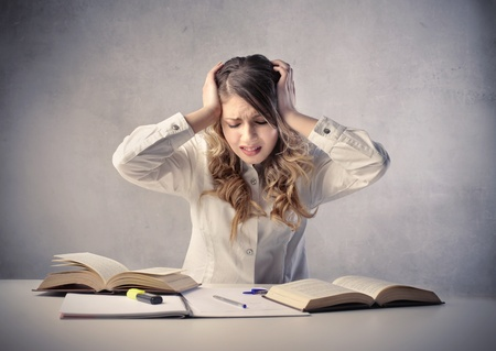 hard working woman: Stressed student in front of some books Stock Photo