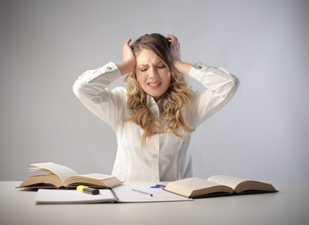 headache: Stressed student sitting in front of some books Stock Photo