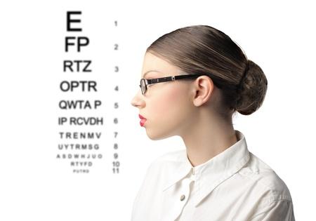 oculista: Perfil de una mujer joven que llevaba gafas con mesa oftálmica a su lado