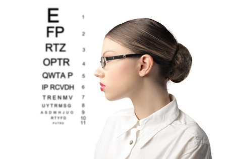 oculist: Profile of a young woman wearing eyeglasses with ophtalmic table beside her Stock Photo