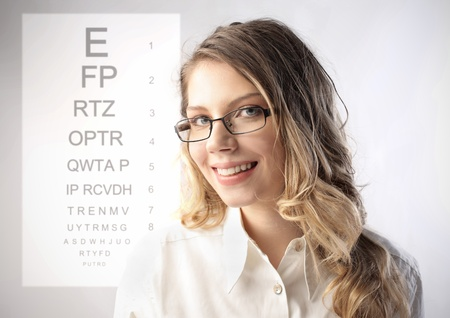 ophthalmic: Smiling eye specialist and ophthalmic table on the background