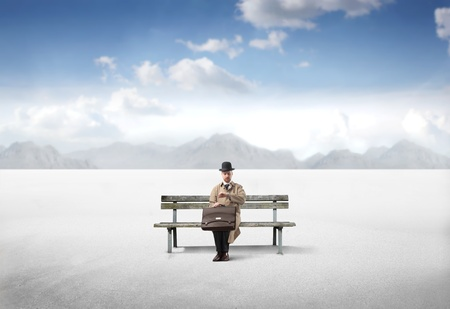 banc de parc: Gentleman assis sur un banc dans un d�sert.