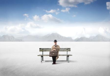 sand watch: Gentleman sitting on a bench in a desert Stock Photo