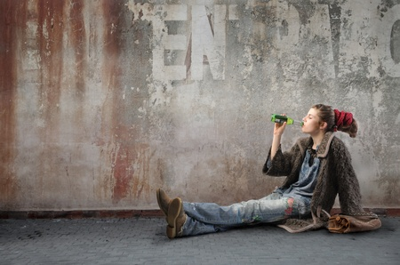 Young woman in alternative clothes drinking a beer photo