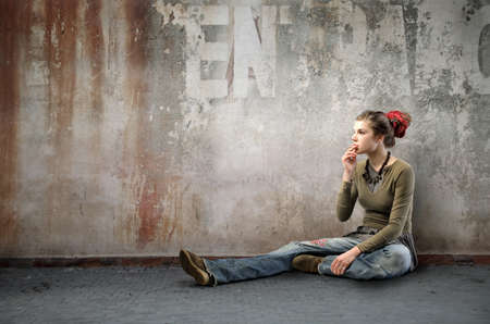 Young woman in alternative clothes smoking a cigarette photo