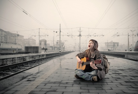 Young woman singing and playing guitar on the platform of a train station photo