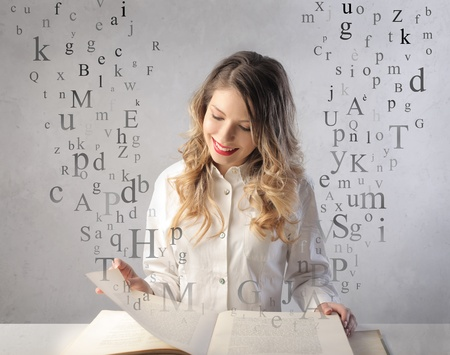 Smiling beautiful woman reading a book with letters flying away from it  photo