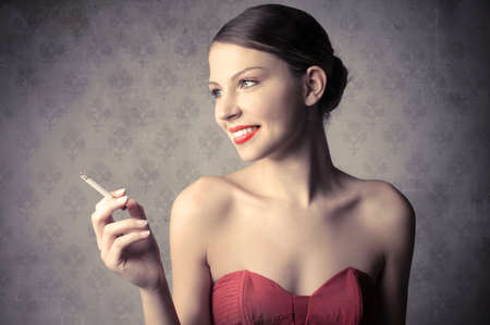 Smiling beautiful woman holding a cigarette photo