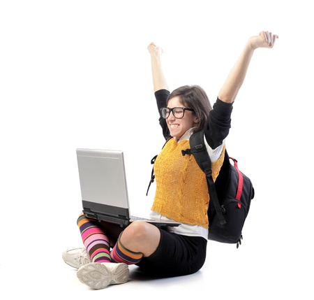 Triumphing young woman with laptop on her knees Stock Photo - 8656295