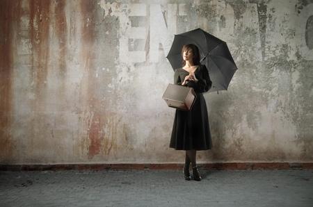 femme avec valise: Belle femme avec parapluie debout contre un mur Banque d'images