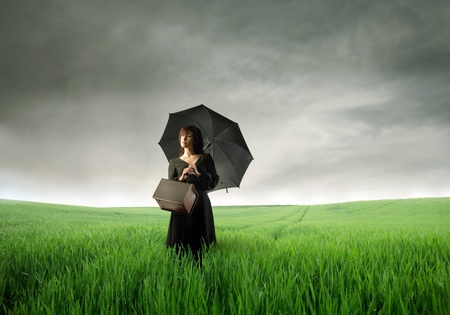 Beautiful woman with umbrella standing on a green meadow photo