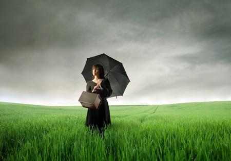 mujer con maleta: Hermosa mujer con paraguas de pie en un prado verde Foto de archivo