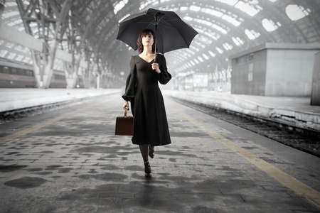woman with umbrella: Beautiful woman with umbrella standing on the platform of a train station