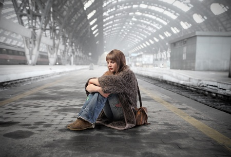 alone girl: Young woman sitting on the platform of a train station