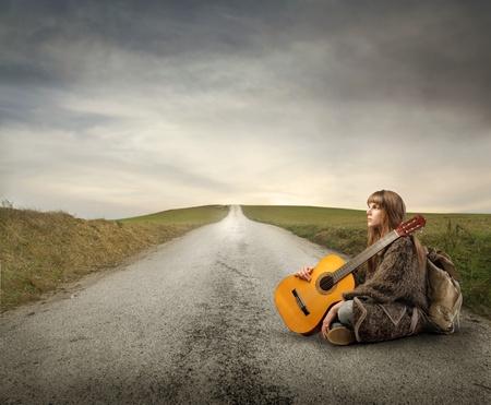 figli dei fiori: Giovane donna con zaino e chitarra seduto su una strada di campagna