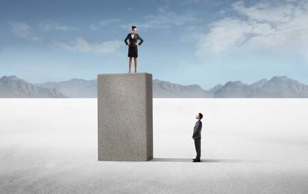 Businessman observing a powerful businesswoman standing higher than him