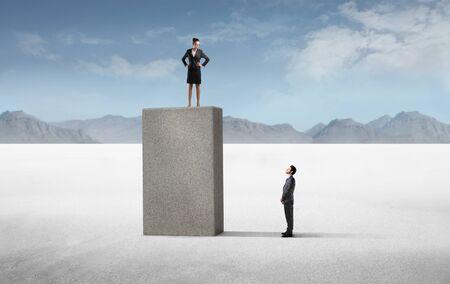 human height: Businessman observing a powerful businesswoman standing higher than him Stock Photo