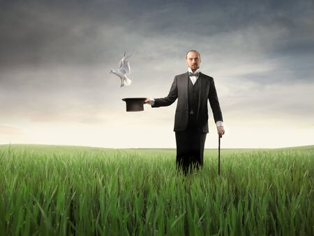Magician with bird flying out from his cylinder hat Stock Photo - 8734689