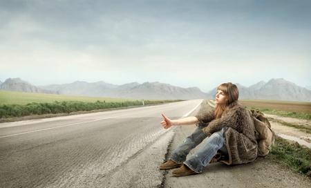 mujer hippie: Kitchhiking de la mujer joven en una carretera de campo Foto de archivo