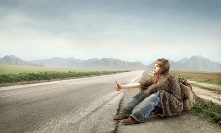 Young woman kitchhiking on a countryside road