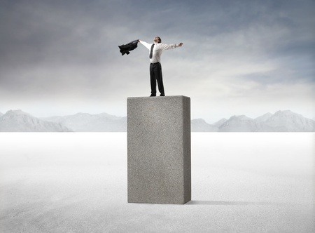triumphing: Businessman triumphing on a high cube