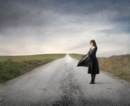 open country: Woman opening an umbrella on a countryside road Stock Photo