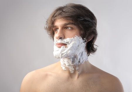 Young man with his visage full of shaving cream photo