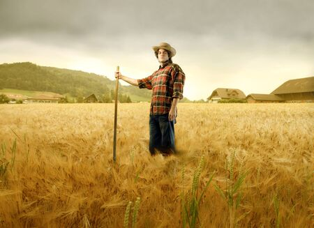 Young farmer standing on a wheat field photo