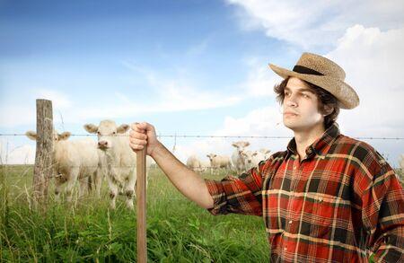joven agricultor: Joven agricultor en un prado verde con animales en el fondo
