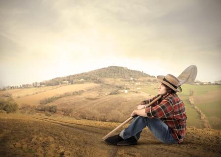 assis par terre: Jeune agriculteur, assis sur une colline Banque d'images