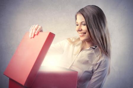 cajas navide�as: Sonriente y bella mujer abrir un regalo Foto de archivo