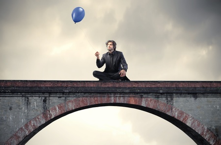 steps to success: Businessman sitting on a bridge and holding a balloon