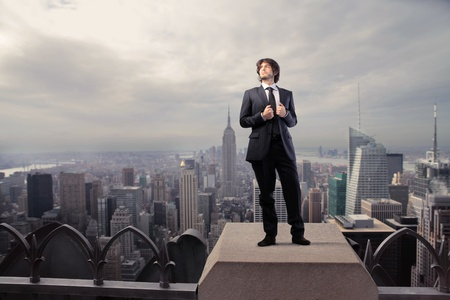 Businessman standing on the rooftop of a skyscraper over a city photo