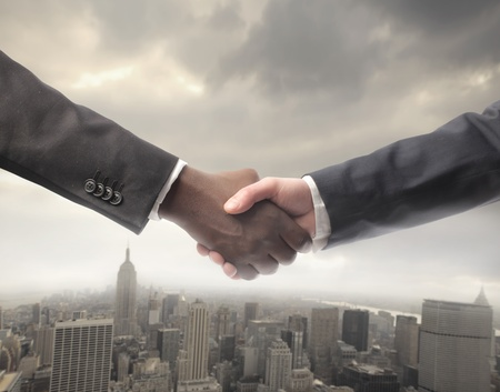 congratulating: African businessmans hand shaking white businessmans hand with cityscape on the backgorund