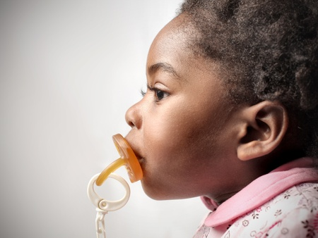 African little girl with pacifier in her mouth Stock Photo - 8738374