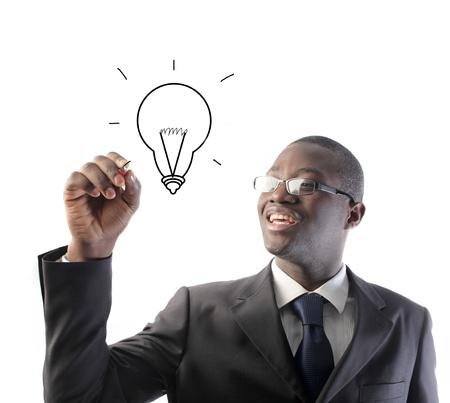 African businessman drawing a light bulb photo