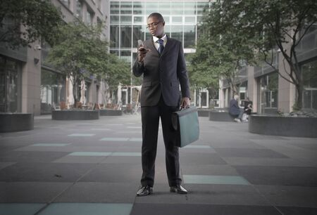 African businessman using a mobile phone on a city street photo