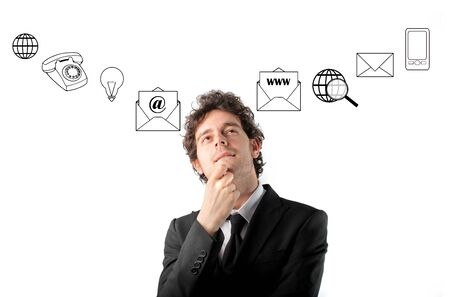 communicate  isolated: Thoughtful businessman with icons on the background Stock Photo